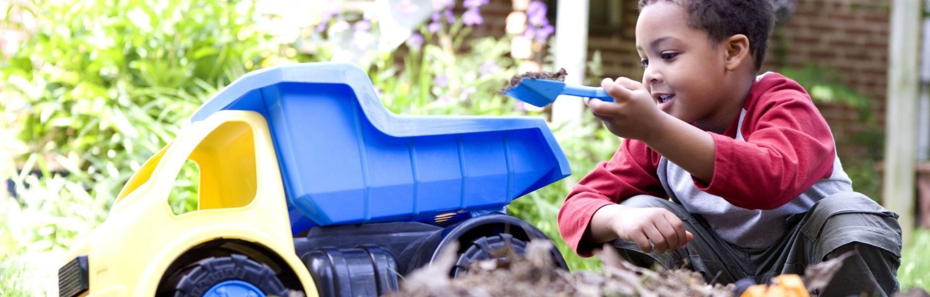 boy playing in the dirt with toy dump truck