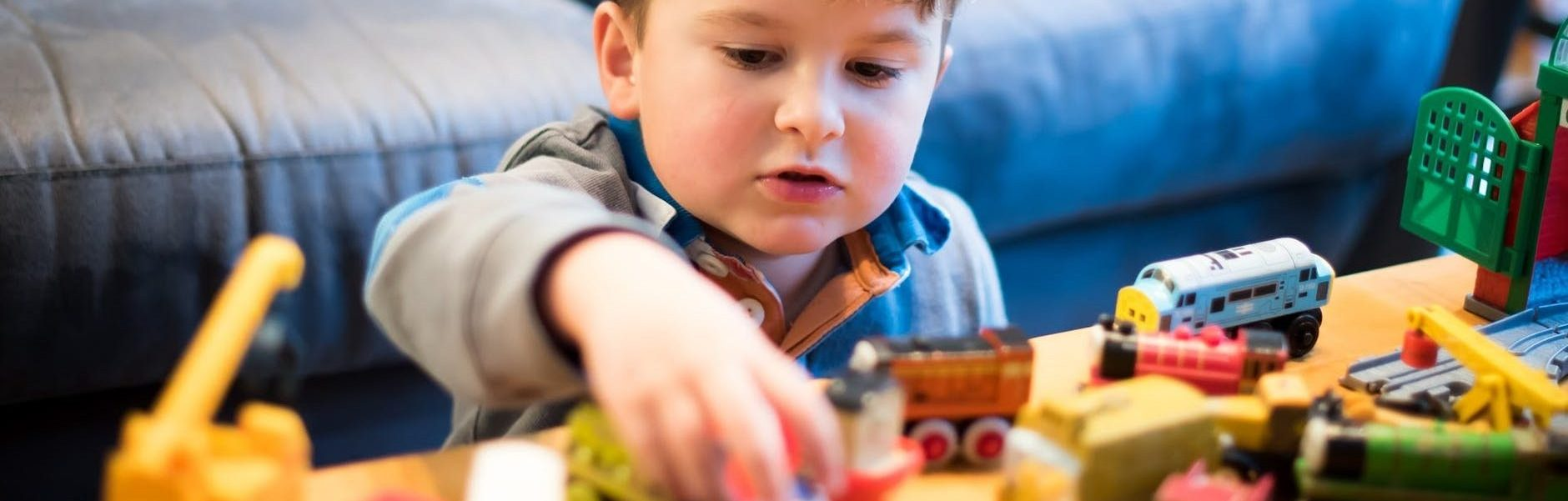 boy plays with toy trains