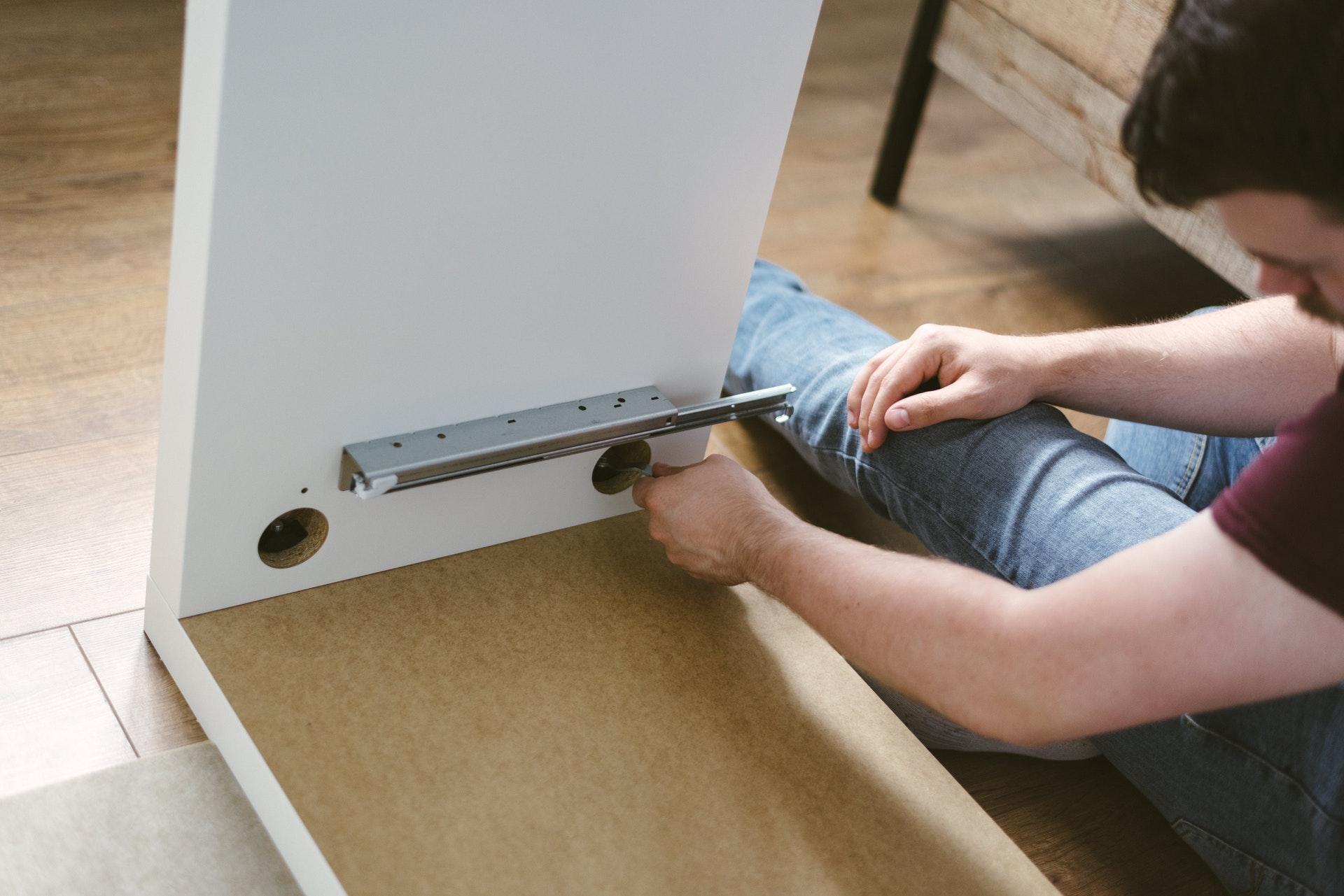 man repairs cabinet