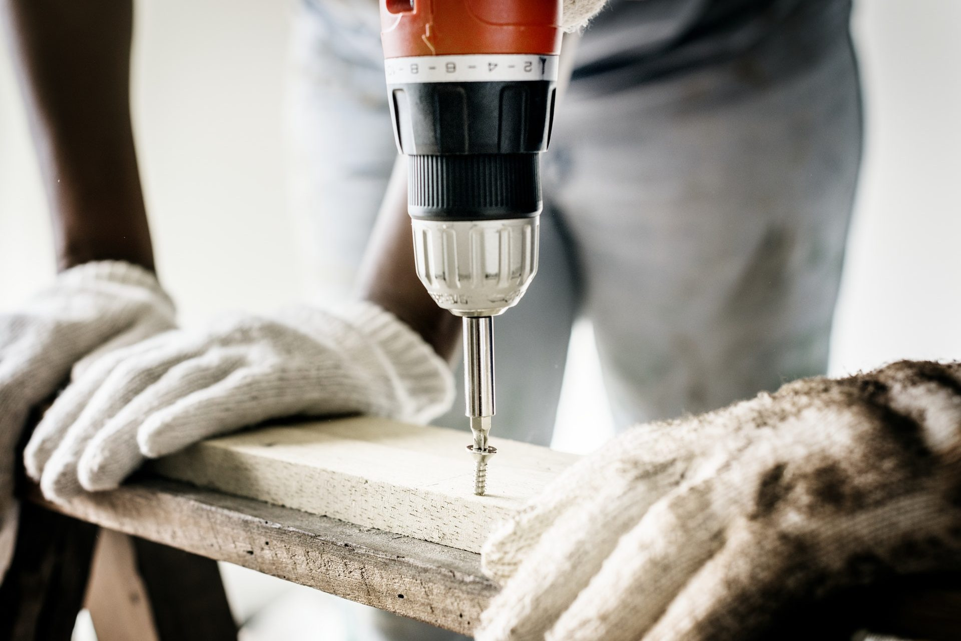 a person drills a screw into a plank of wood